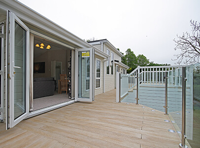 AB Sundecks Wood Effect Decking and Picket Glass surrounding a Lodge